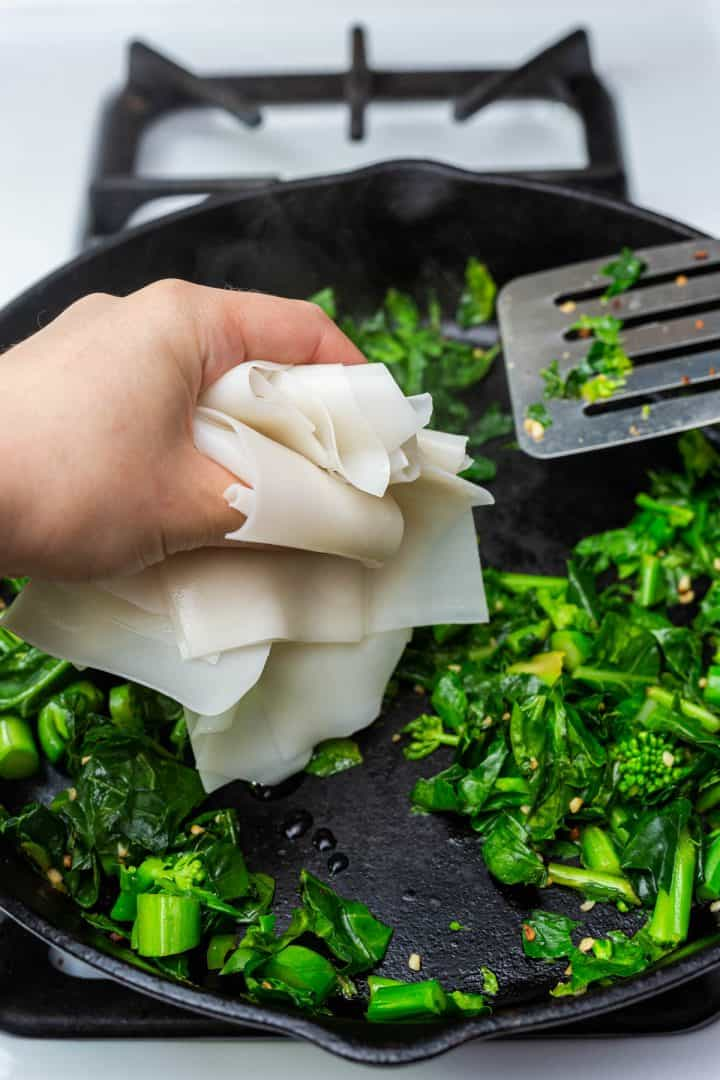 Hand placing handful of cooked wide rice noodles in cast iron pan with Chinese broccoli on stove