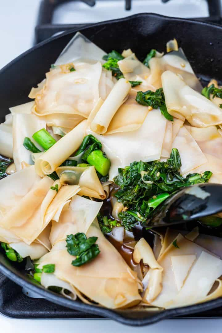 Rice flake noodles and Chinese broccoli in cast iron pand