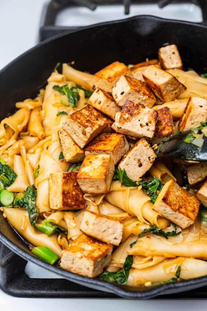 Tofu Pad See Ew in cast iron pan on stove