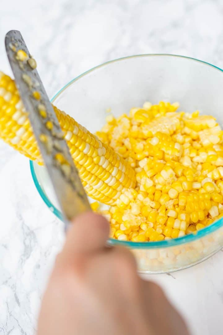 Hand with knife cutting kernels off ear of corn into bowl