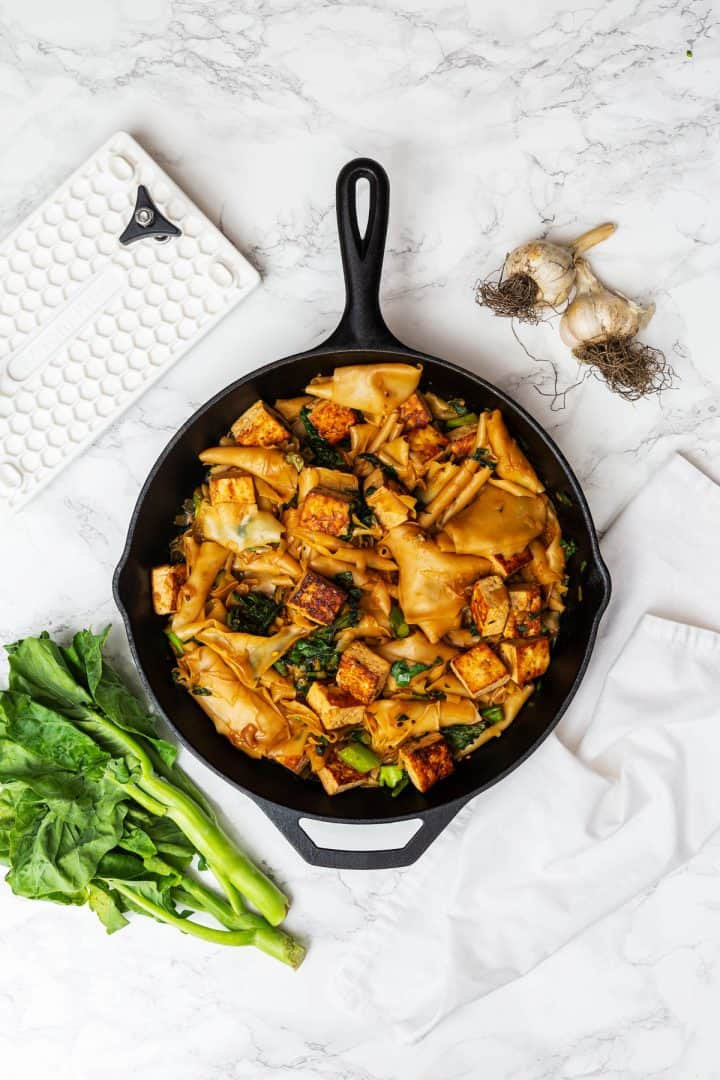 Pad See Ew in cast iron pan on counter with Chinese broccoli and garlic off to side