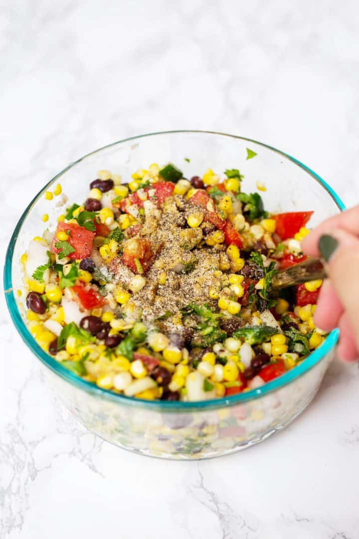 Hand mixing spices into corn salsa