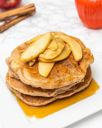 Plate of apple pancakes with syrup with cinnamon sticks and apple in background