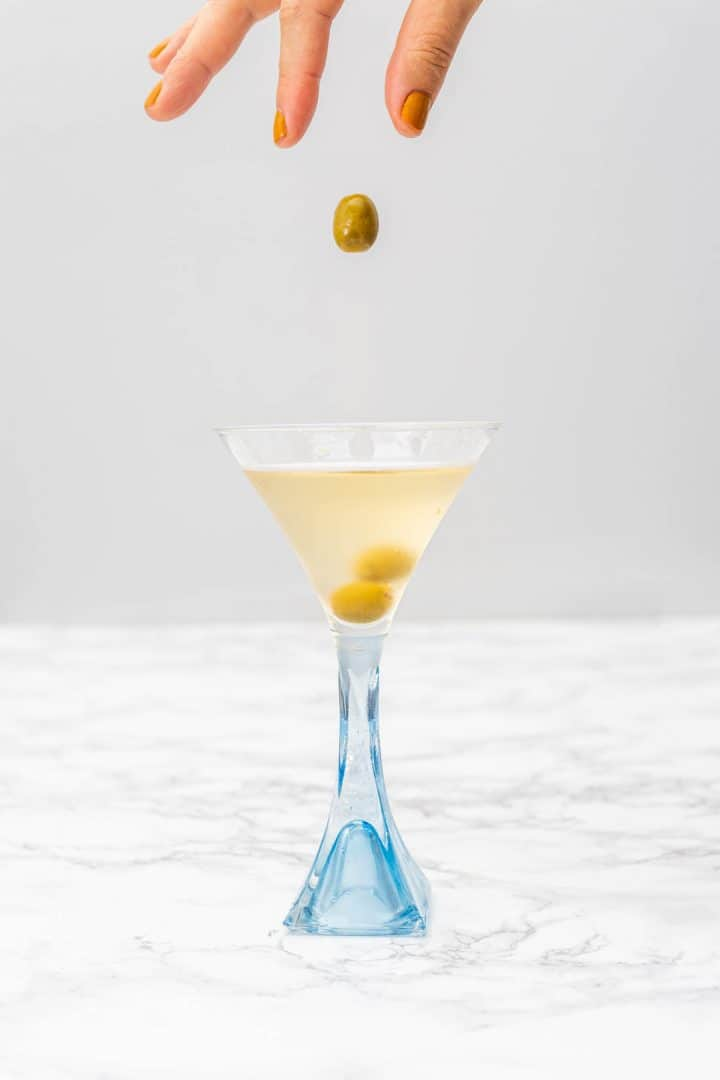 Hand dropping olive into gin martini