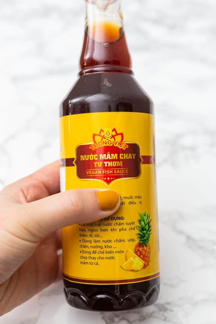 Hand holding bottle of vegan fish sauce
