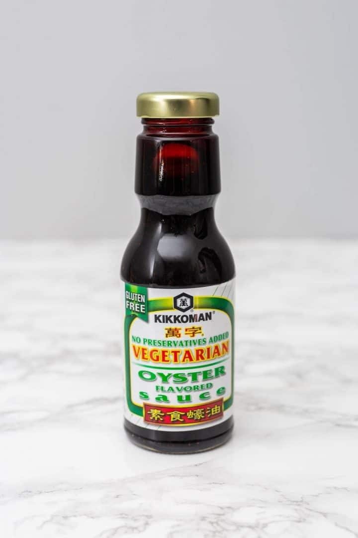 Bottle of Kikkoman Vegetarian Oyster sauce on white marble counter with gray background