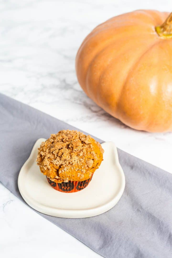 Pumpkin muffin on small white plate shaped like a cat face with gray cloth napkin and pumpkin in background