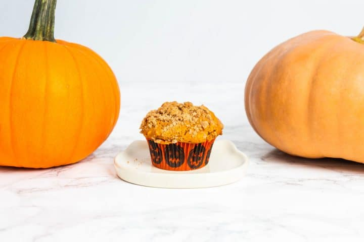 Pumpkin muffin on small plate with two pumpkins on either side