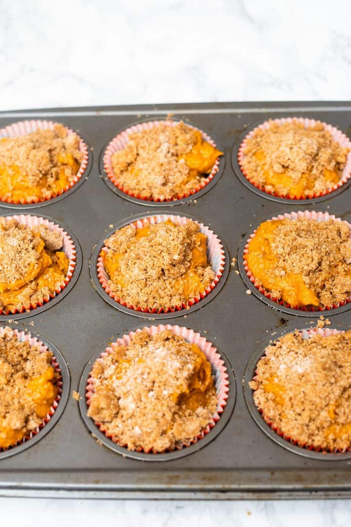 Unbaked pumpkin muffins in tray topped with streusel