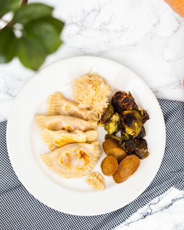 Plate of pierogi with roasted brussels sprouts, sauerkraut, and veggie sausage surrounded by fall decor