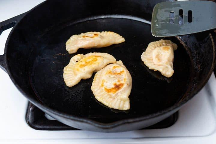 Pan fried pierogi in large cast iron pan on stove