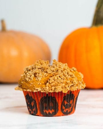 Close up of pumpkin muffin on table with pumpkins in background