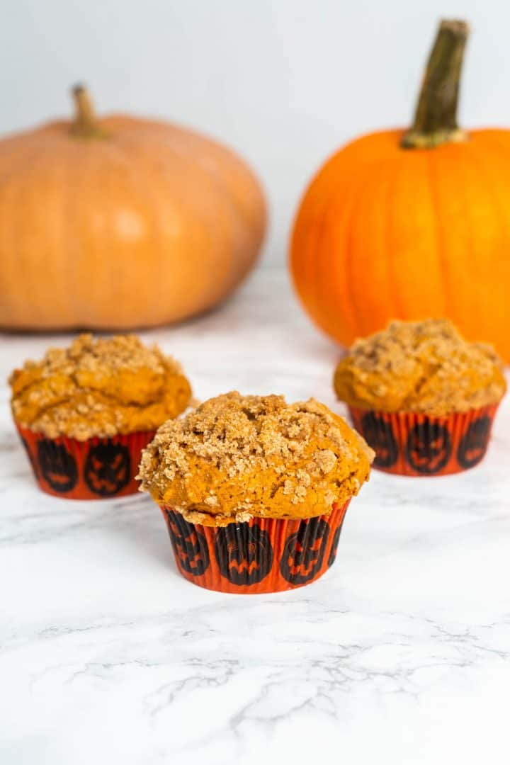 Three pumpkin muffins on table with pumpkins in the background