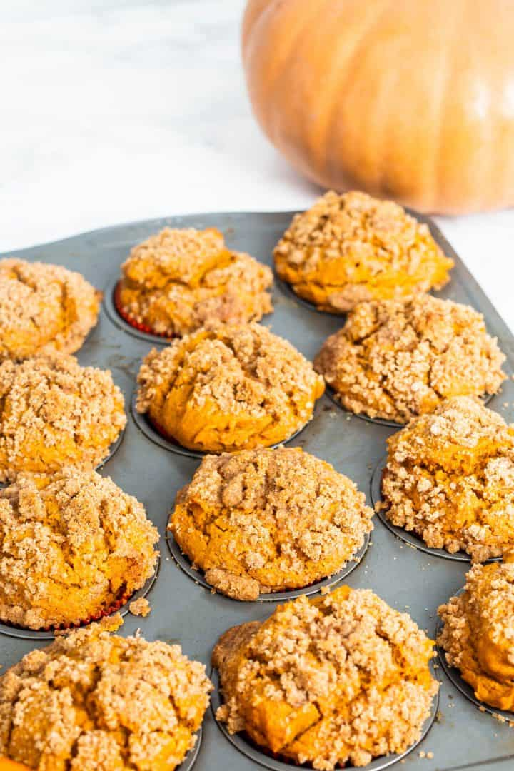 Tray of baked pumpkin muffins with pumpkin off to side