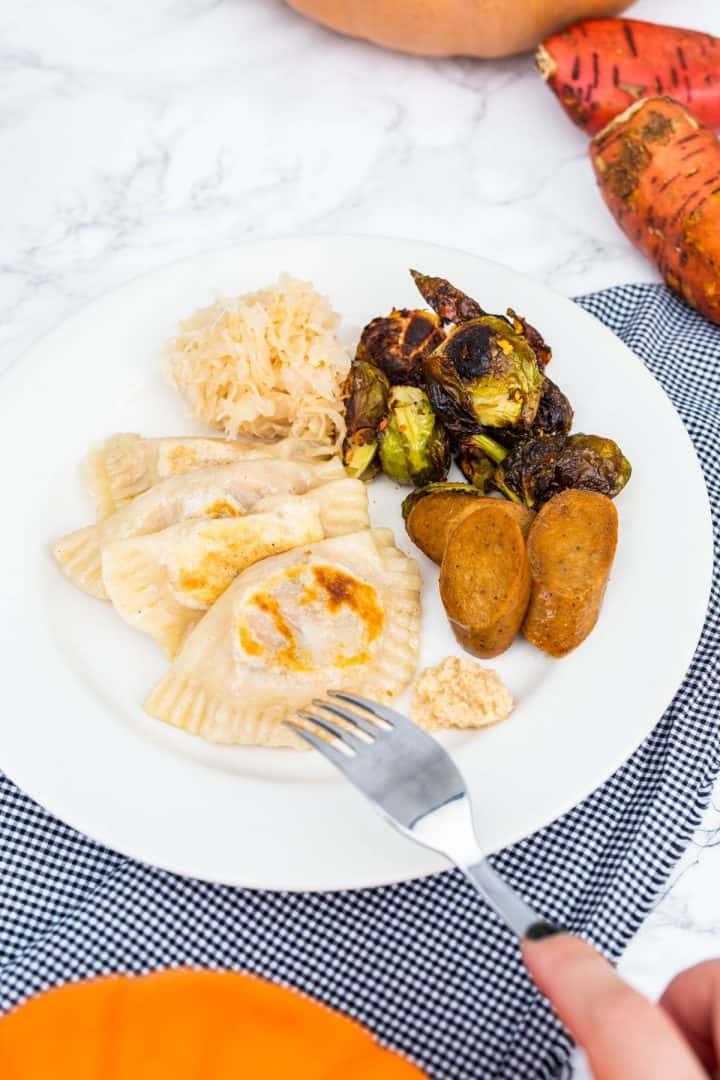 Hand holding fork over plate of pierogi with side dishes surrounded by pumpkins and sweet potatoes